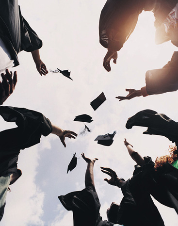 college graduates throwing caps into the air
